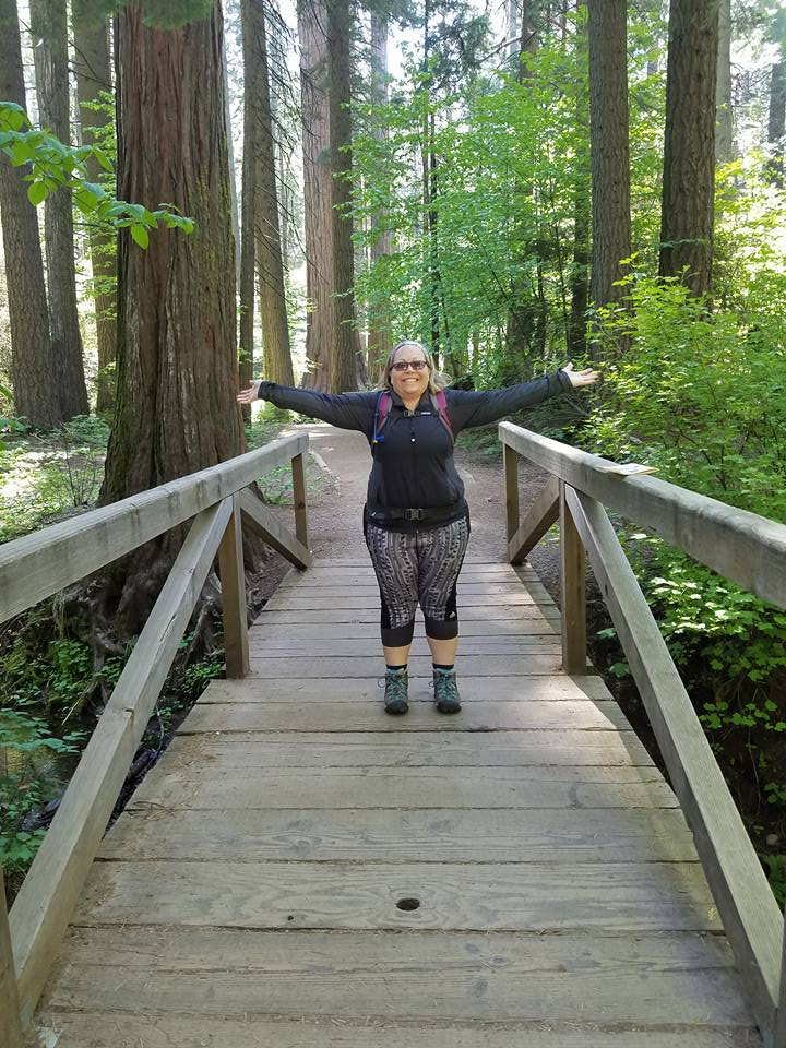ms hamilton standing on a wooden bridge in the middle of the forrest
