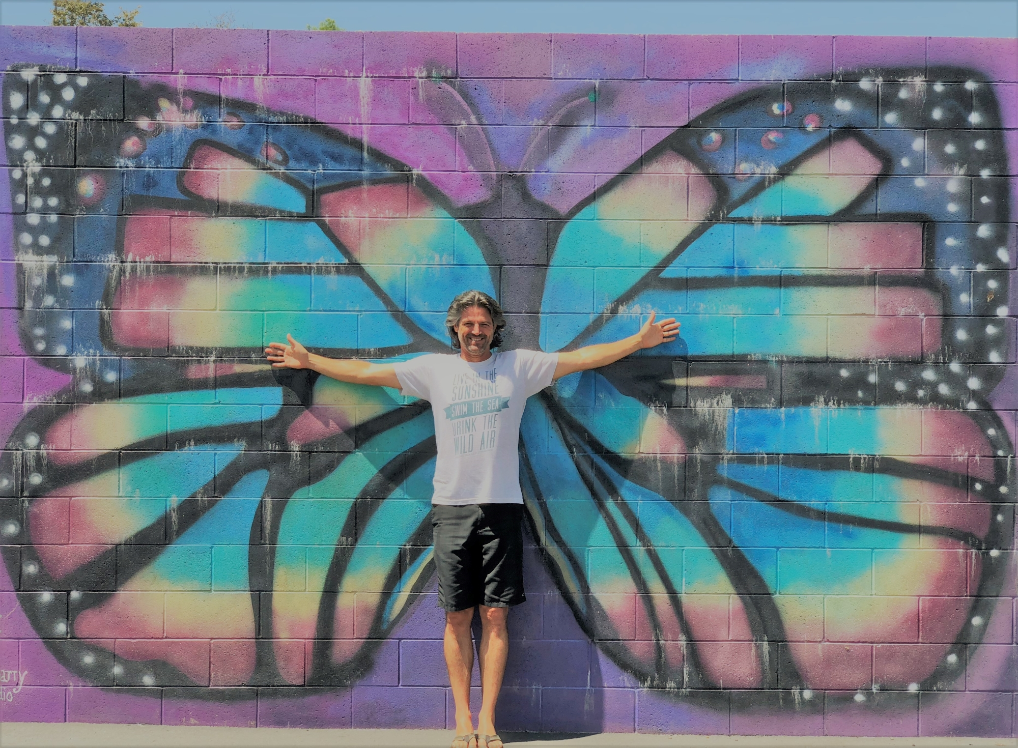 Mr. Retzer standing in front of the butterfly wall on the playground