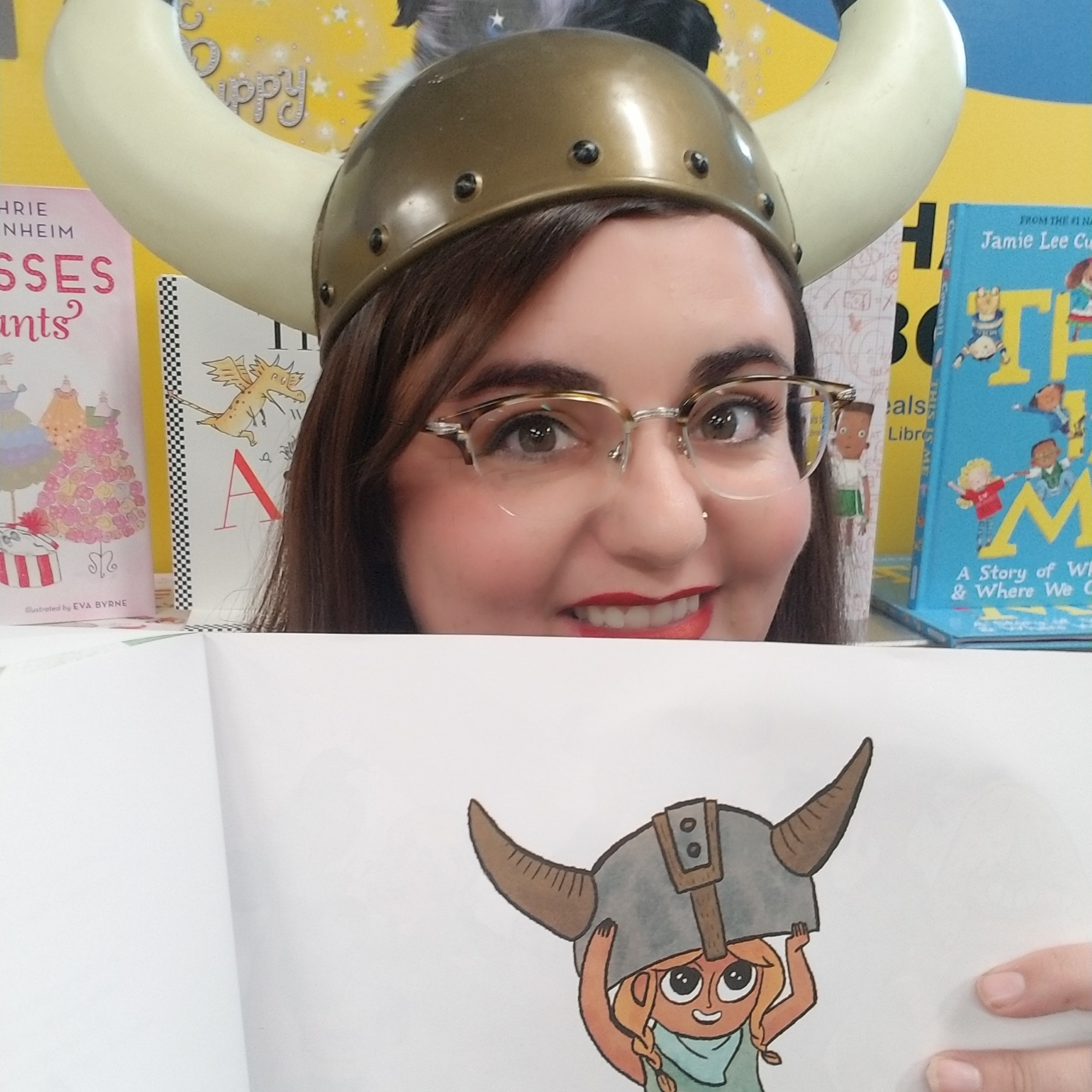 Woman with dark hair, glasses, and a Viking helmet with horns holds open a children's book featuring a character wearing the same kind of hat.